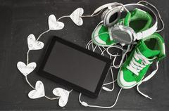 love for music concept. green sneakers, headphones, tablet and hearts. - stock photo