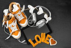 love for music concept.orange sneakers, headphones, tablet and hearts - stock photo