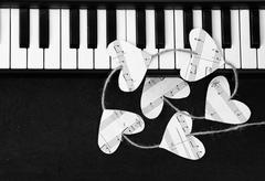 piano keys and hearts of the music on a black background - stock photo