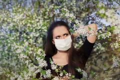Woman with Allergy with Respirator Mask in Spring Blooming Decor - stock photo