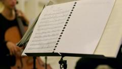Tracking shot of string quartet from music sheet to musician - stock footage