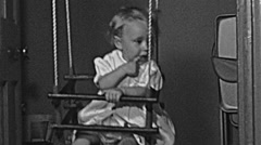 England 1949: baby swinging on a seesaw - stock footage