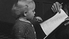 England 1949: baby watching a book's page Stock Footage