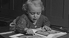 England 1949: baby watching pictures of a book Stock Footage