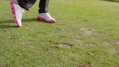 Close up, pan around shot of golfer swinging and hitting golf ball - Slow Motion Stock Footage