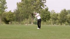 Wide, front on shot of golfer striking ball up the fairway Stock Footage