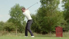 Front view of professional golfer teeing off Stock Footage