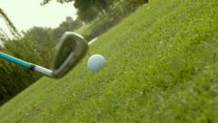 Rotating, ground level, close up shot of golf ball being struck - Slow Motion Stock Footage