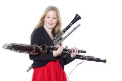young girl holds woodwind instruments in studio - stock photo