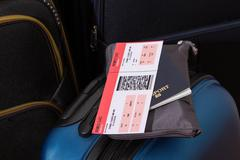 airline ticket, passport and luggage - stock photo