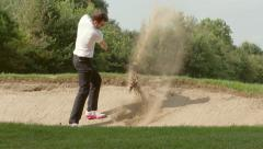 Golfer swinging and hitting golf ball out of sand trap/bunker Stock Footage