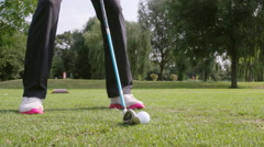 Ground level shot of golfer swinging and hitting golf ball Stock Footage