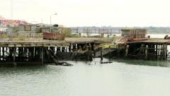broken old disused pier with large ship in background - stock footage