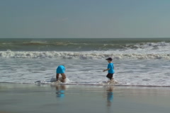 Two boys playing along Cocoa Beach Stock Footage