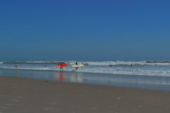 Surfers heading into Cocoa Beach water - stock footage