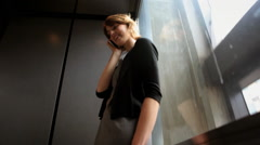 Young business woman riding elevator an elevator talking on phone Stock Footage