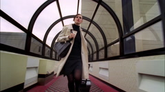 Young business woman running through airport terminal Stock Footage