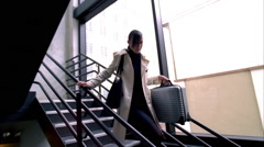 Young business woman running down stairwell with business case Stock Footage