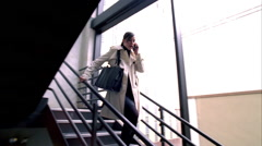 Young business woman running down stairwell while talking on mobile phone Stock Footage