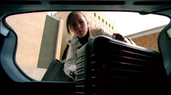 Young business woman putting rolling business case in car trunk Stock Footage