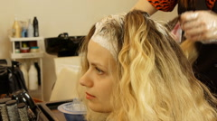 beautician applying color dye to woman's hair - stock footage
