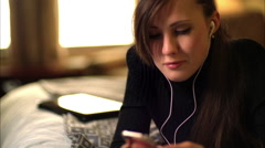Attractive young woman lying on her bed listening to music Stock Footage