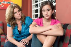 Worried and sad mother looks at her teen daughter Stock Photos