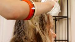 Young woman having her hair dyed by beautician - stock footage