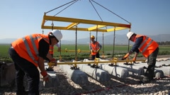 Mechanics install steel reinforced concrete railway sleepers Stock Footage