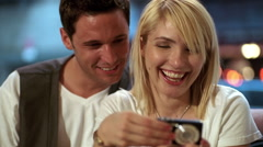 Young urban couple looking at photos on their digital pocket camera in a cafe Stock Footage