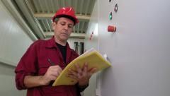 Engineer Writing in Plant Electrical Room Stock Footage