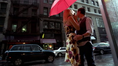 Young urban couple walking through the rain under umbrella in the city Stock Footage