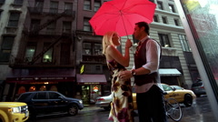 Young urban couple running through the rain under umbrella in the city Stock Footage