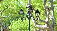 OLD STYLE LAMPS IN ST TROPEZ PARK Stock Footage