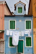 Sky blue little house in burano with white sheets and clothes hanged out Stock Photos