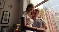Portrait of an urban couple sitting on the window ledge of their apartment Stock Footage