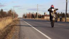 Dirtbike wheelie on the road Stock Footage