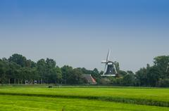 windmill behind farmland horizontal - stock photo