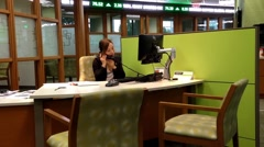 Manager answering phone for customer inquiry inside td bank Stock Footage