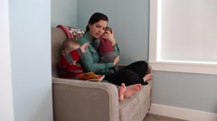 A mom reading story books with toddler and baby Stock Footage