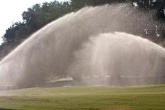 Sprinklers douse golf course fairway with water Stock Photos
