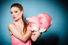 Stock Photo of female boxer wearing big fun pink gloves playing sports