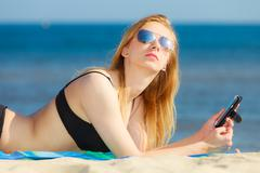 Summer vacation girl with phone tanning on beach Stock Photos