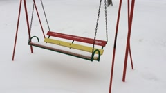 Empty swing metallic chains in winter time with snow. Stock Footage
