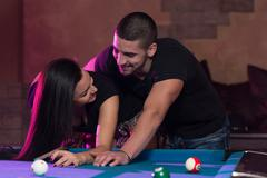 boy and girl flirting on a pool game - stock photo