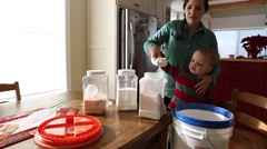 Toddler helping mother put flour in food container Stock Footage