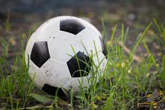 Battered old soccer ball, slightly deflated, in long grass of unmowed footbal Stock Photos