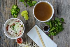 Pho fast food to go on wood background with peppers and basil Stock Photos