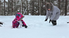 Mother helping young daughter to roll snowballs for making snowman Stock Footage