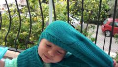 Cute baby takes of his balaclava Stock Footage